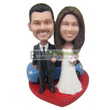 groom in black suit and bride in white wedding dress with their blue car bobbleheads