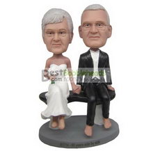 groom in black suit and bride in white wedding dress sitting on the chair bobbleheads