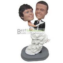 groom in black suit holding bride in white wedding dress bobbleheads