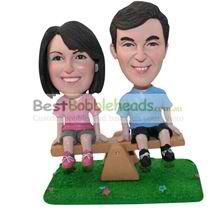 custom couple sitting on a teetertotter figurines